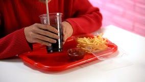 Вода женского клиента выпивая carbonated от пластикового стекла, нездорового обеда стоковые фото