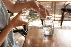 Вода женщины лить в стекло на деревянном столе стоковая фотография rf