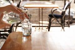 Вода женщины лить в стекло на деревянном столе стоковые изображения rf