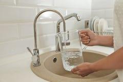 Вода женщины лить в стеклянный кувшин в кухне стоковые фотографии rf
