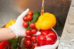 Вода из крана пропуская на красном болгарском перце и splasing на томате стоковые изображения rf