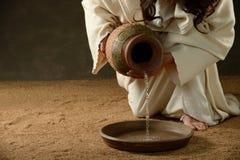Вода Иисуса лить от опарника стоковая фотография