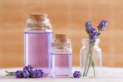 Вода и масло лаванды в стеклянных бутылках и свежей лаванде цветут на пне и коричневой предпосылке Стоковая Фотография