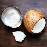 Вода кокоса в стекле и треснутой гайке кокосов на темном деревянном ба Стоковые Фотографии RF
