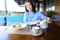 Вода очаровательного клиента ресторана лить в чашку стоковое фото rf