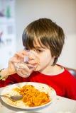 Вода питья ребенка и спагетти еды Стоковое Фото