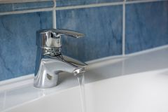 Вода пропуская от водопроводного крана в ванной комнате Стоковое Фото