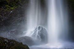Вода ударяет валуны на основании водопадов Стоковое Изображение