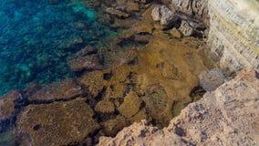 Вода Teal, берег мустарда, скала Tan стоковые фотографии rf