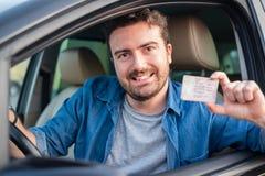 Водительское право показа человека усаженное в автомобиль стоковые фото