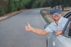 Водитель автомобиля при стекла виртуальной реальности показывая большие пальцы руки вверх на Стоковое фото RF