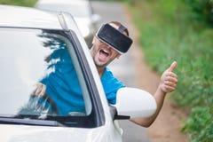 Водитель автомобиля при стекла виртуальной реальности показывая большие пальцы руки вверх на Стоковые Изображения RF