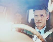 Водитель в роскошном автомобиле с женщиной на задних сиденьях Стоковые Изображения RF