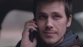 Водитель говоря по телефону в автомобиле