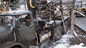 Водитель грузовика вставляет вне окно смотря грузоподъемник проходя мимо видеоматериал