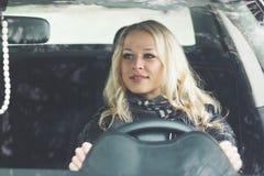 Водитель женщины в автомобиле держит колесо автомобиля Стоковые Фотографии RF