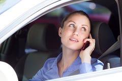 Водитель женщины используя мобильный телефон Стоковые Изображения RF