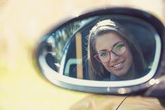 Водитель женщины смотря в зеркале взгляда со стороны ее нового автомобиля стоковые фотографии rf