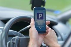Водитель используя приложение смартфона для того чтобы оплатить для парковать стоковые фотографии rf