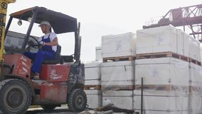 Водитель платформы грузоподъемника в фабрике или складе управляя между строками Shelving с стогами коробок и упаковкой