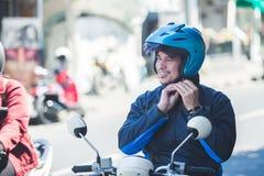Водитель такси мотоцикла прикрепляя его шлем для катания безопасности стоковая фотография