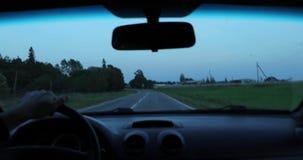 Водитель управляет автомобилем и камера снимает ее изнутри автомобиля видеоматериал