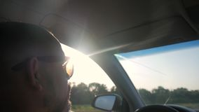 Водитель управляя автомобилем едет вдоль дороги, ярких лучей блеска солнца Профиль молодых красивых приводов человека акции видеоматериалы
