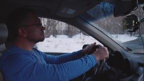 Водитель человека управляет в стопах города на высокой скорости после этого и открепляет ремень безопасности сток-видео
