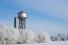 Водонапорная башня маленького города, освещенная солнечным светом против замороженные ландшафты стоковое фото