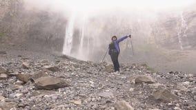 Водопады падают высокий в горах Женщина идет сток-видео