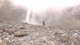 Водопады падают высокий в горах Женщина идет видеоматериал