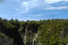 Водопад на большой возвышенности, окруженной деревьями стоковое фото rf