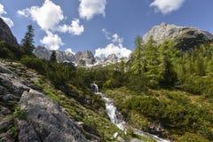 Водопад на озере Seebensee на пути от деревни Ehrwald к хате Coburger с горной цепью на заднем плане, Тироль, Austri Стоковые Изображения