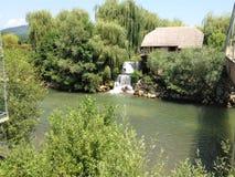 Водопад с домом на заднем плане стоковое изображение rf