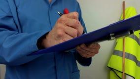 Водопроводчик в голубых прозодеждах писать отчет о доску сзажимом для бумаги сток-видео