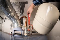 Водопроводчик использует ключ для труб на горячем нагревателе воды для того чтобы завинтить гайку металла стоковая фотография rf