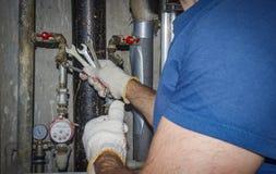 Водопроводчик ремонтирует трубы и трубопровод Профессиональный работник с ключем на предпосылке канализационных трубов, манометро стоковые изображения