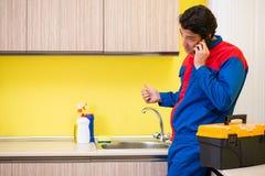 Водопроводчик ремонтируя кран на кухне стоковые изображения