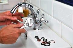 Водопроводчик ремонтируя faucet с ключем стоковые фото