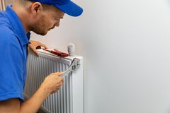 Водопроводчик установки системы отопления дома устанавливая радиатор стоковая фотография rf
