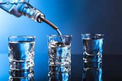 Водочка лить от бутылки в стекло в баре стоковая фотография