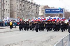 Военная аркада с большое количество музыкантов в черном парадном костюме с латунными аппаратурами и русскими флагами во время пар стоковое фото rf