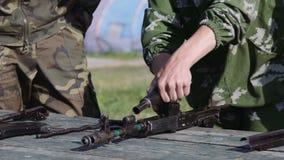 Военная подготовка: кадет в камуфлировании собирает демонтирует AK-47 акции видеоматериалы