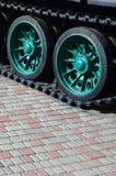 Военное транспортное средство на следах гусеницы стоит на квадрате вымощая камней Фото зеленых гусениц с металлом катит то Стоковое Фото