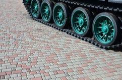 Военное транспортное средство на следах гусеницы стоит на квадрате вымощая камней Фото зеленых гусениц с металлом катит то Стоковое Изображение RF