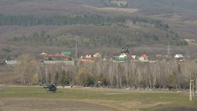Военный вертолет русской военновоздушной силы принимает на фоне гор северного Кавказ видеоматериал