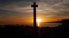 Военный мемориал принятый против заходящего солнца на clifftop в Англии стоковое изображение