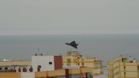 Военный самолет летая над зданиями пасмурный день в airshow акции видеоматериалы