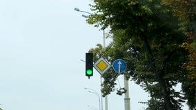 Вождение автомобиля вдоль улицы города на зеленом светофоре, предупредительном знаке дороги, управлении сток-видео