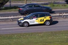 Вождение автомобиля управляя школы AA на дороге стоковые фото